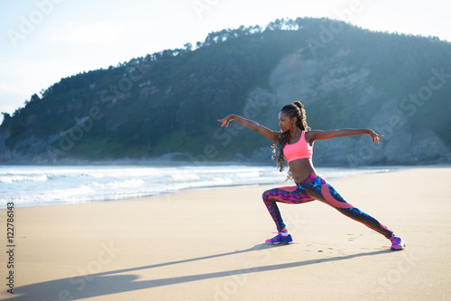 Fototapeta Fitness woman stretching legs and practicing dancing poses at the beach. Black female athlete working out outdoor against the sea.