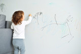 Fototapety Curly cute little baby girl drawing with crayon color on the wall. Works of child