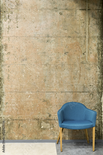 Blue chair in front of a concrete wall with copy space © interiorphoto