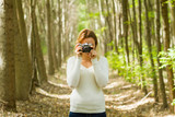 woman taking photo in the forest