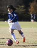 Young girl playing soccer dribbling with ball