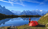 Fototapety Hiker enjying the view at his red tent in the mountains near Chamonix, France.