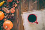 red cup of tea on wooden table, autumn decor, sackcloth, pumpkins, fruits, top view