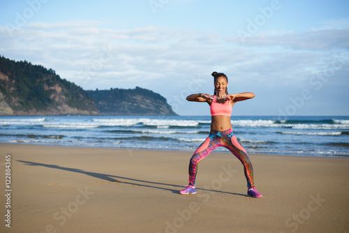 Sporty brazilian woman dancing and having fun at the beach. Black happy dancer enjoying music rhythm. - 122884365