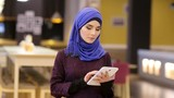 Muslim woman in contemporary oriental clothes working with electronic tablet
