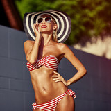 Hot beautiful tanned woman in sunhat and bikini