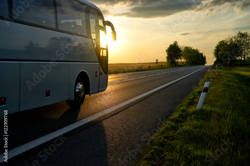 White Bus driving along the asphalt road in a rural landscape at sunset