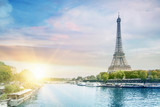 Fototapety Romantic sunset background. Eiffel Tower with boats on Seine river in Paris, France.