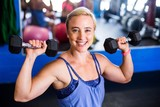 Portrait of happy woman lifting dumbbell in gym