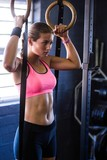 Woman holding gymnastic rings in gym