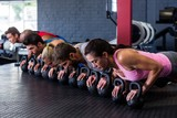 People doing push-ups with kettlebell in gym