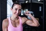 Smiling female athlete lifting kettlebell