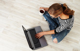 Young woman with coffee mug sitting on the floor with laptop. Concept of distant work, lifestyle and technology.