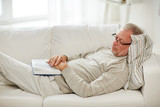 senior man sleeping on sofa with book at home