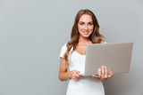Happy attractive young woman standing and holding laptop