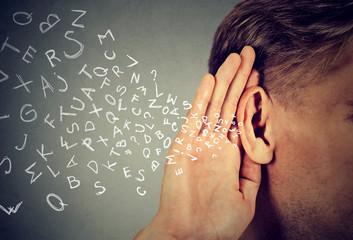 man holds hand near ear listens carefully alphabet letters flying in