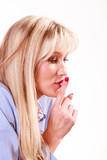 Woman face in profile with finger gesture silence.