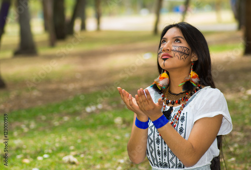 Staande foto Kameleon Beautiful Amazonian woman with indigenous facial paint and white traditional dress posing happily for camera in park environment, forest background