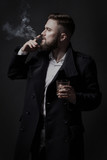 Attractive bearded man in a black coat smoking a cigar with pleasure. He holds a glass with some drink. He is stylish, strong and masculine, a cloud of cigar smoke rises above it.