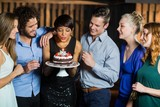 Woman blowing the candle on her birthday cake