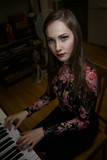 Portrait of a beautiful girl playing the piano