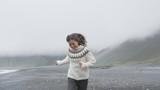 Cheerful happy woman having fun running on Iceland beach laughing joyful and playful wearing Icelandic sweater on black sand beach. Female model girl enjoying nature landscape at ocean sea. RED EPIC.