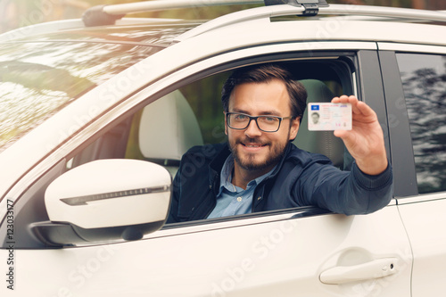 Poster young happy man showing his new driver license