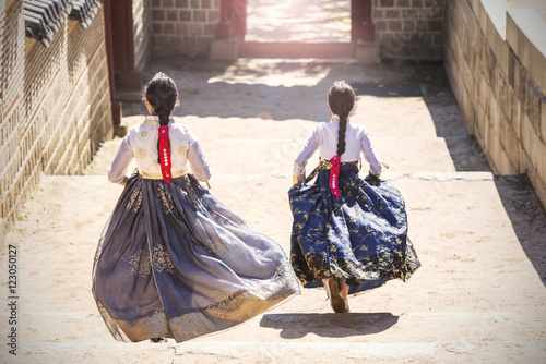 Two Korean Girls dressed in traditional dress running down stairs in Seoul stree