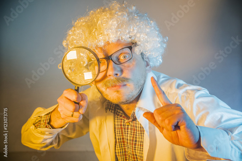funny scientist, like Einstein with a magnifying glass плакат