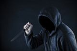 Hooded man with knife in the dark