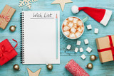 Cup of hot cocoa or chocolate with marshmallow, holiday decorations and notebook with wish list on turquoise vintage table from above, christmas planning concept. Flat lay style.
