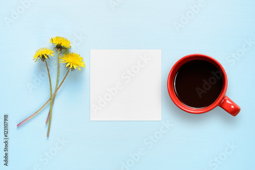 Dandelion flowers, blank paper and coffee cup on blue table top view