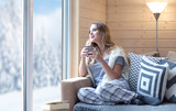Fototapety Young beautiful blonde woman with cup of coffee sitting home in living room by the window. Winter snow landscape view. Lazy day off concept