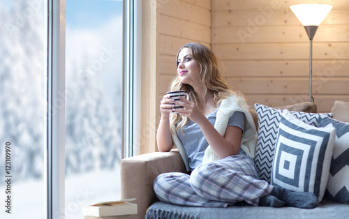 Young beautiful blonde woman with cup of coffee sitting home in living room by the window. Winter snow landscape view. Lazy day off concept - 123109970