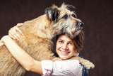 beautiful young woman with a dog on a dark background. Hug. High
