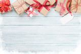 Christmas wooden background with gift boxes and snow