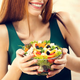 Beautiful young woman eating salad, indoor