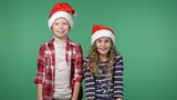 Cute boy and girl in christmas caps tossing up confetti, green screen background