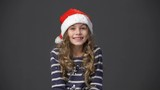 Cute little girl in a christmas cap throwing up confetti, gray background