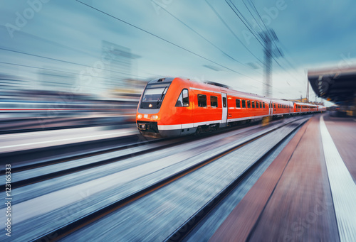 Nowoczesne wysokiej prędkości czerwony pasażer pociągiem podmiejskim w ruchu na platformie kolejowej. Stacja kolejowa. Kolej z efekt rozmycia ruchu. Przemysłowy pojęcie krajobraz z instagram tonowaniem. Transport