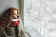 Cute little girl sitting with a cup of hot cocoa by the window a