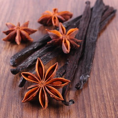 Fragrant vanilla and star anise on wooden surface plank