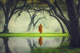 Monk hike in deep forest reflection with lake, Buddha Religion c - 123185760