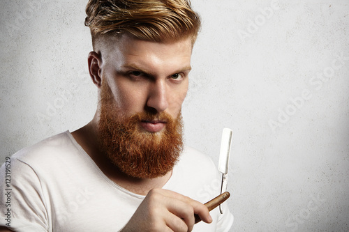 Headshot of attractive professional barber with thick red beard and mustache, holding razor Poster