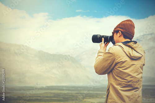 Poster travel photographer journalist holding a dslr camera in mountain background (Vin