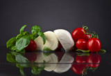 mozzarella with green basil and tomatoes on black table
