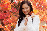 Beautiful smiling girl in colorful autumn leaves