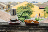 Vietnamese coffee and croissant on the table
