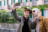 Couple of friends outdoor in the city taking selfie with smart phone hand hold outdoor in the city, smiling - vanity, social network, communication concept