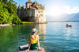 Young female traveler enjoying great view on Chillon castle sitting on the pier on Geneva lake in Switzerland